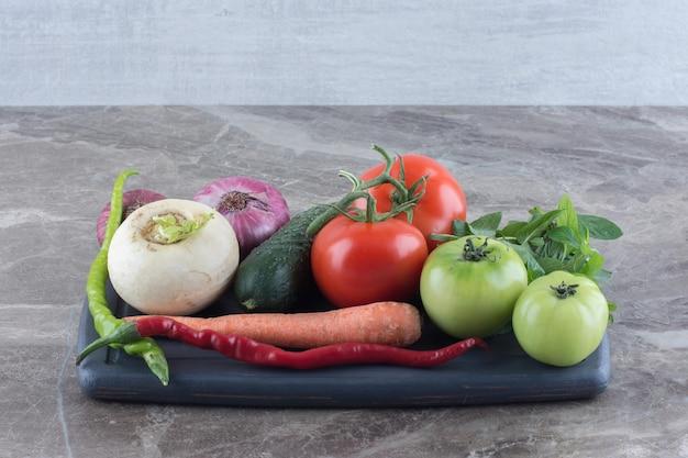 Schotel van komkommer, wortel, rode en groene tomaten, witte raap, groene en rode paprika, rode uien en munt op marmeren oppervlak