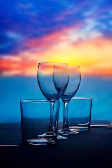 Schotel van kopjes en kristallen glazen op zee zonsondergang