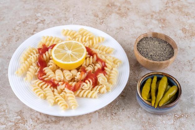 Schotel van macaroni met kleine schaaltjes zwarte peper en ingelegde paprika's op marmeren oppervlak