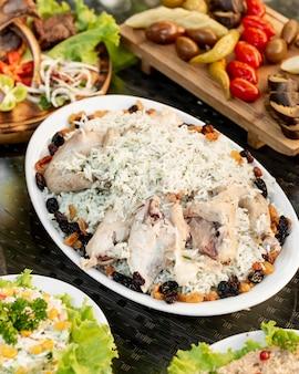 Schotel van rijst met dille geserveerd met kippenvleugels en gedroogde vruchten