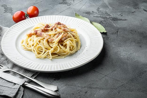 Schotel van spaghetti carbonara, modern italiaans recept van pasta met guanciale, ei en pecorino romano kaas set, op grijze stenen tafel, met kopie ruimte