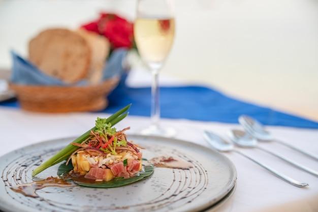 Schotel van tonijnsalade op eettafel met champagne voor diner in restaurant.