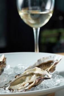 Schotel van verse oesters geserveerd in ijs met witte wijn