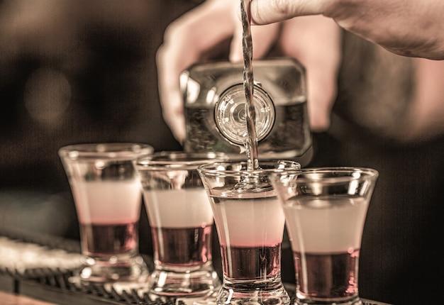 Schoten in de nachtclub. rode alcoholische drank in glazen op bar. rode cocktail in de nachtclub. barman die cocktailschutter voorbereidt.