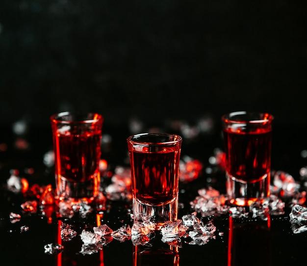 Schoten met rode drankjes op tafel