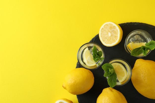Schoten met schijfje citroen en munt op dienblad op geel oppervlak