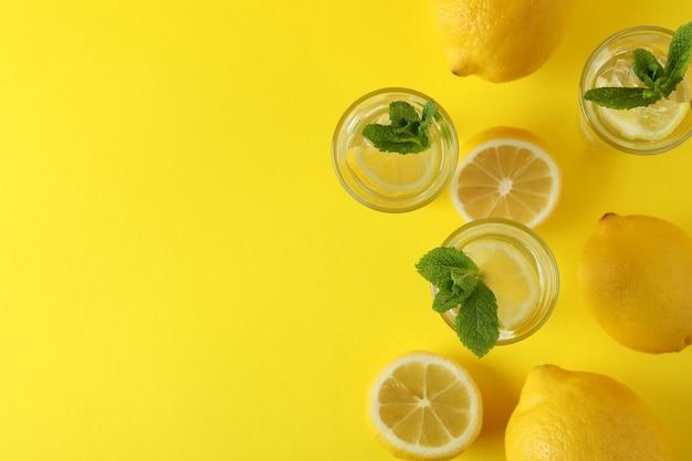 Schoten met schijfje citroen en munt op geel oppervlak