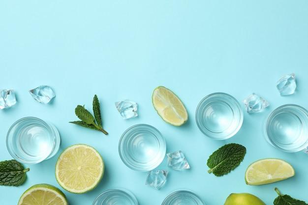 Schoten, schijfjes limoen, munt en ijsblokjes op blauwe muur, bovenaanzicht