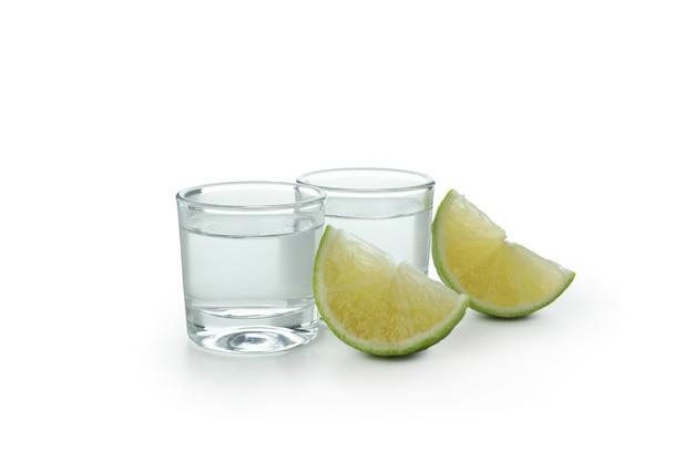 Schoten van wodka en limoenplakken die op wit worden geïsoleerd