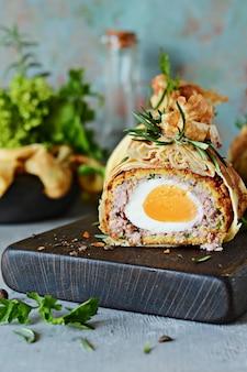 Schotse eieren in een pannenkoekenzak met groen op een grijsblauwe achtergrond een klassiek gerecht in een onconventionele portie heerlijk en smakelijk gerecht uit de britse keuken