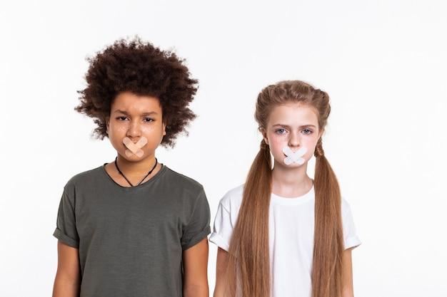 Schouder aan schouder. emotionele sprakeloze kinderen die problemen met de vrijheid van meningsuiting uiten terwijl ze hun mond bedekten