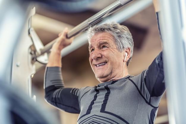 Schouderkracht uitoefenen door een oudere man op een fitnessapparaat in de sportschool.