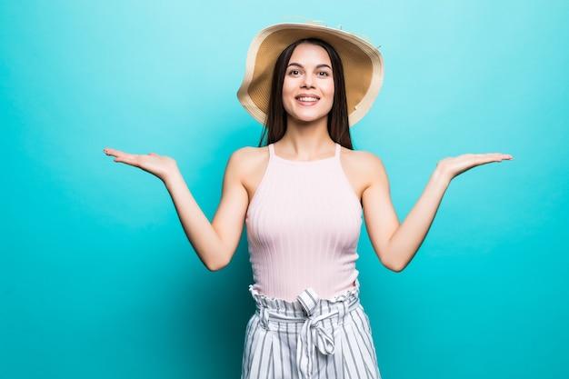 Schouderophalende vrouw in twijfel doet schouderophalend toont open handpalmen, gebarend, kijk naar kant geïsoleerd op blauwe muur.