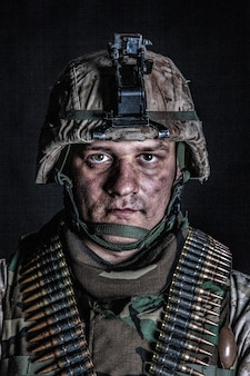 Schouderportret van ervaren legersoldaat, militaire conflictveteraan, bekwame marinejager in haveloze camouflage-uniform, geavanceerde helm en munitieriemen op de borst, studio-opname op zwarte achtergrond