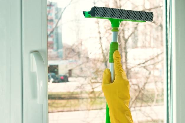Schraper voor het reinigen van ramen in het groen op de achtergrond van het raam