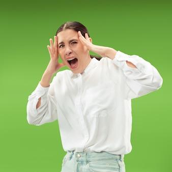 Schreeuwen, haat, woede. huilende emotionele boze vrouw die op groene studioachtergrond gilt.