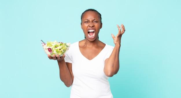 Schreeuwen met de handen in de lucht en een salade vasthouden