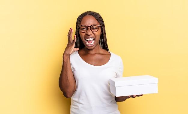 Schreeuwen met de handen in de lucht, woedend, gefrustreerd, gestrest en overstuur voelen en een lege doos vasthouden