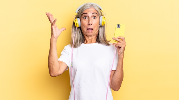 Schreeuwen met de handen in de lucht, woedend, gefrustreerd, gestrest en overstuur voelen met een koptelefoon
