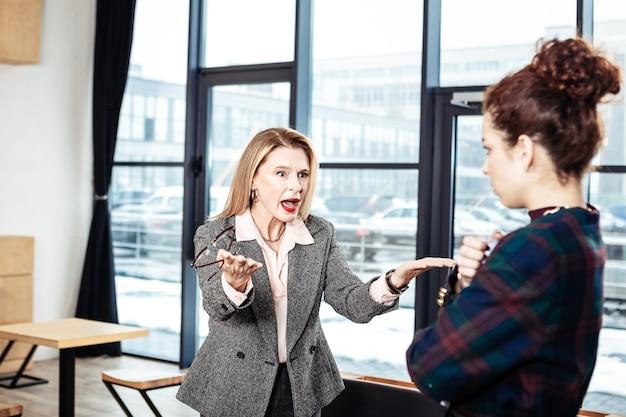 Schreeuwen tegen secretaresse. emotionele zakenvrouw met rode lippen die tegen haar nieuwe luie secretaresse schreeuwt
