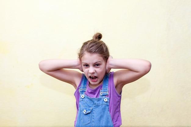 Schreeuwend bang pre-tienermeisje dat haar oren met haar handen behandelt