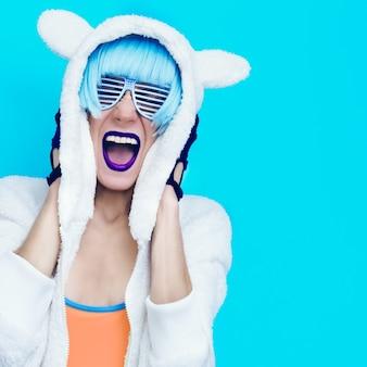 Schreeuwend gek meisje in hoodie teddy bear op een blauwe achtergrond.