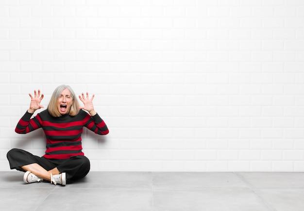 Schreeuwend in paniek of woede, geschokt, doodsbang of woedend, met de handen naast het hoofd