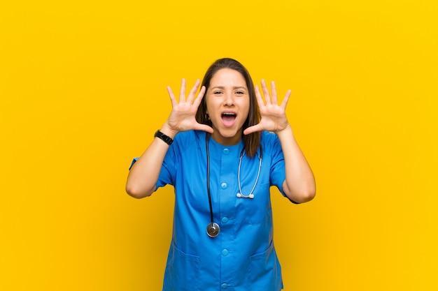 Schreeuwend in paniek of woede, geschokt, doodsbang of woedend, met handen naast hoofd geïsoleerd tegen gele muur