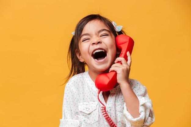 Schreeuwend opgewonden meisje kind praten door rode retro telefoon.