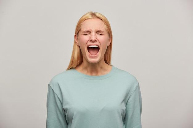 Schreeuwende blonde vrouw kijkt bang bang, imiteer schreeuw, schreeuw, sla een luide oproep uit of huil