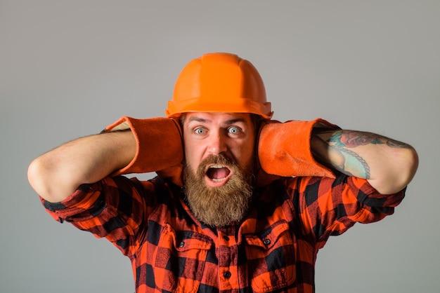 Schreeuwende bouwer in bouwvakker adverteert reparatiewerkman bouwer in werkhandschoenen bouwindustrie