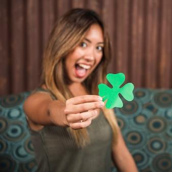 Schreeuwende gelukkige vrouw die groenboekklaver houdt