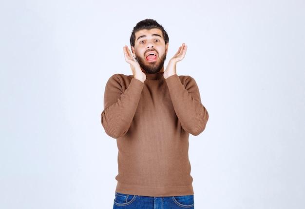 Schreeuwende jonge bebaarde man in casual schreeuwen geïsoleerd