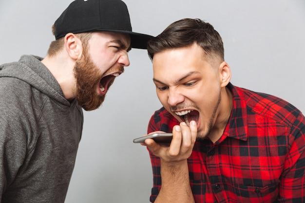 Schreeuwende jonge twee mannen praten via de telefoon.