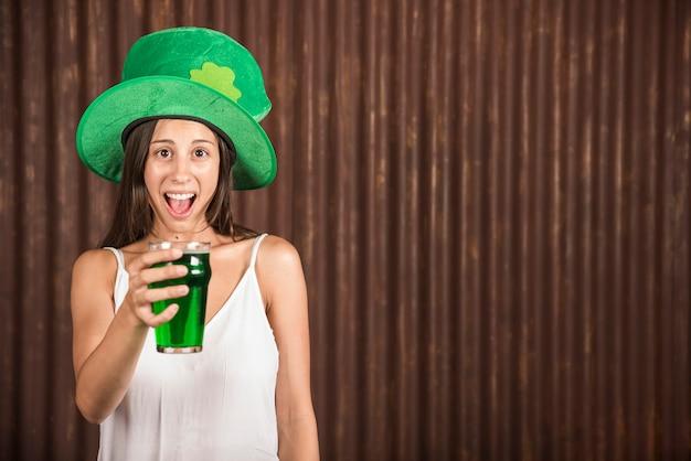 Schreeuwende jonge vrouw die glas van drank toont