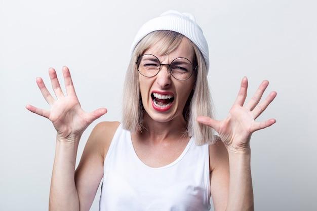 Schreeuwende jonge vrouw schrikt in glazen, witte hoed op een lichte achtergrond.