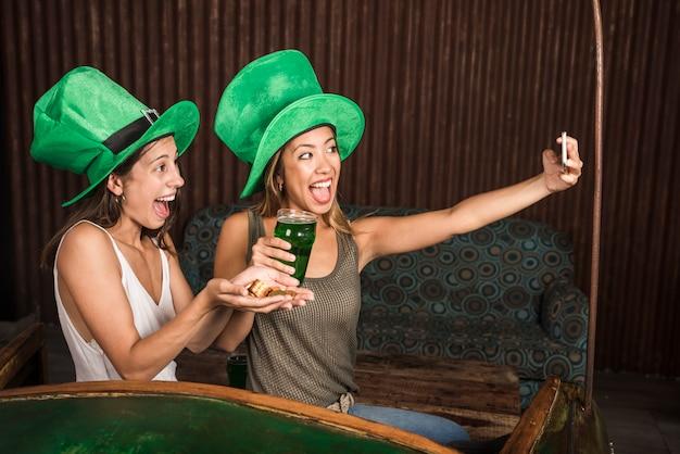 Schreeuwende jonge vrouwen met glas drank en gouden muntstukken die selfie op smartphone nemen
