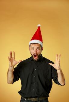 Schreeuwende kerst man met een kerstmuts op een oranje achtergrond