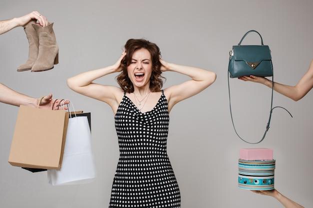 Schreeuwende koper jonge mode vrouw poseren kiezen van kleding, accessoires en schoenen