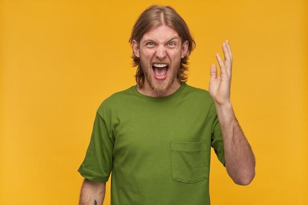 Schreeuwende mannelijke, ontevreden bebaarde man met blond kapsel. groen t-shirt dragen. heeft tatoeages. steekt zijn hand op en schreeuwt van woede. geïsoleerd over gele muur