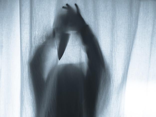 Schreeuwende menselijke drukken door middel van stoffen gordijn als horror achtergrond