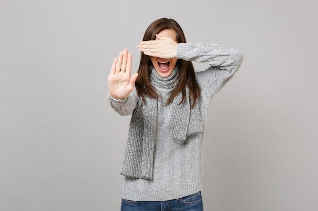 Schreeuwende vrouw in trui sjaal die ogen bedekt met de hand met stopgebaar met palm geïsoleerd op een grijze achtergrond. gezonde mode levensstijl mensen emoties, koude seizoen concept. bespotten kopie ruimte.