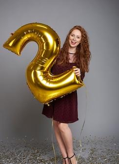 Schreeuwende vrouw met ballon die haar bedrijf tweede verjaardag viert
