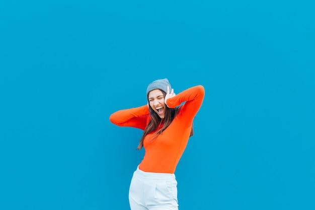 Schreeuwende vrouw met haar handen op oor die gebreide hoed over blauwe achtergrond dragen