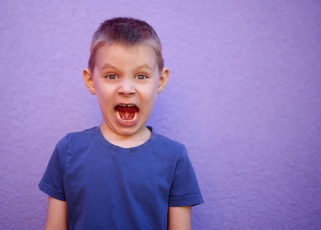 Schreeuwende zesjarige jongen in een blauw t-shirt op een paarse achtergrond