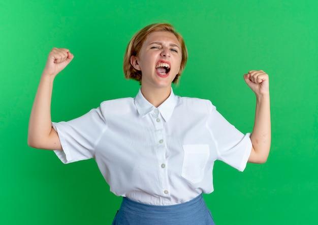 Schreeuwt het jonge, woedende blonde russische meisje met opgeheven vuisten