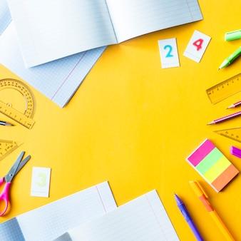 Schriftboeken, pennen, potloden, cijfers en linialen op een gele achtergrond