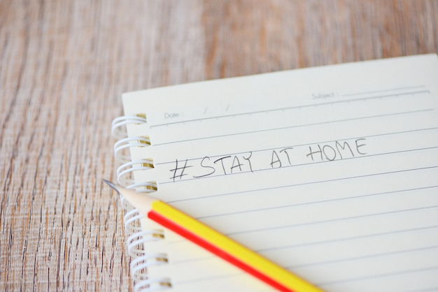 Schrijf woorden blijf thuis op notebookpapier met potlood pandemie van coronavirus of covid-19 en sociale afstand houden thuis blijven met zelfquarantaine om uitbraak te stoppen en virusverspreiding te beschermen