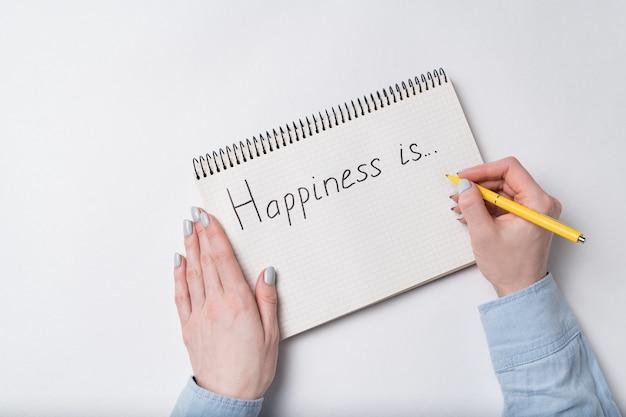Schrijfboek met geluk is tekst. bovenaanzicht van vrouwelijke handen schrijven in notebook