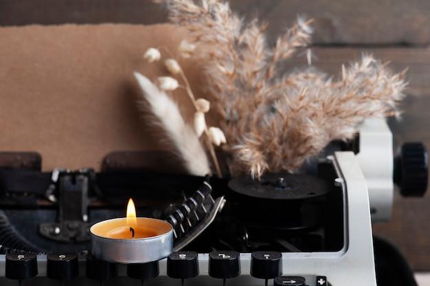 Schrijfmachine close-up en droge bloemen met verlichte aroma kaars. valentines concept, vintage afgezwakt en kraftpapier
